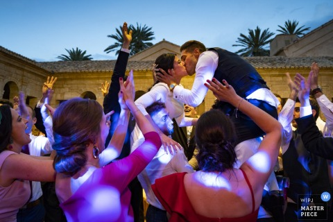 Bride and groom kiss as they are lifted into the air outside at the wedding reception in Cartuja de Ara Christi