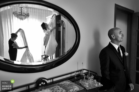 Reggio Calabria Wedding Photographer - Bride hanging her dress as her father watches