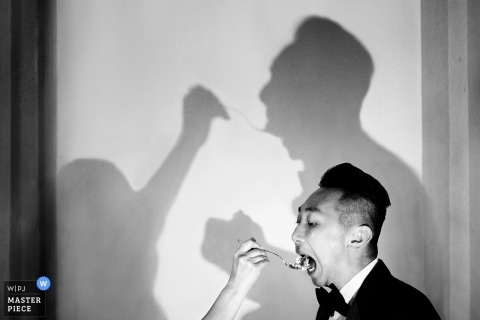 Bride feeds the groom wedding cake at the reception in Castello di Meleto, Gaiole in Chianti, Tuscany and their shadows are cast on the wall.