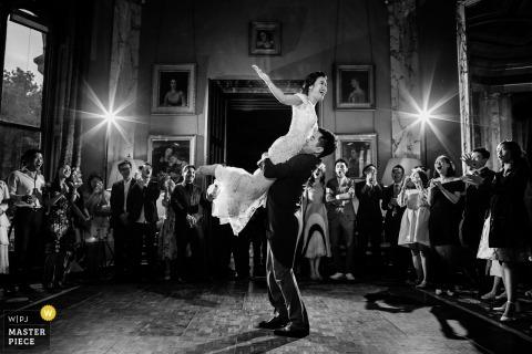 Bruidegom verheft de bruid tijdens het dansen op de bruiloftsreceptie in het Sudeley Castle, Verenigd Koninkrijk