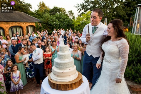 Outdoor photo of the bride and groom about to cut the cake at the wedding reception at the Dodford Manor, Northamptonshire, United Kingdom