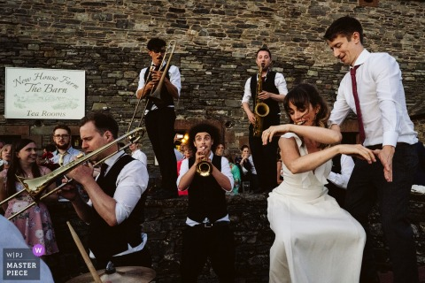 Bride and groom dance around the band at the wedding reception in Lake district, UK