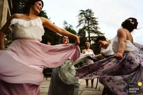 Bride and bridesmaids dance outside at the wedding reception at Lake district, UK