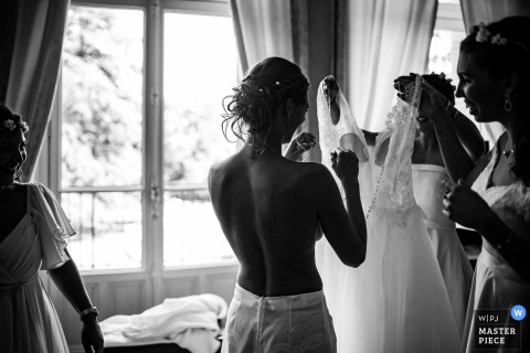 Bridesmaids helping the bride with her dress before the wedding ceremony in Clos des Tourelles