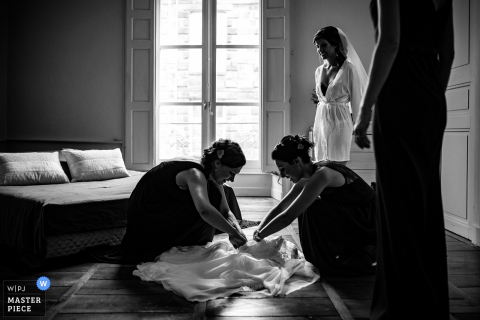 Bride gets help with her wedding dress before putting it on in Riom