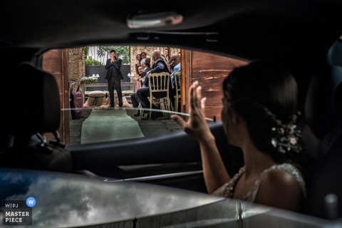 Calabria bride waves from inside the car at the wedding