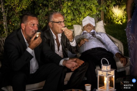 Guest sleeps on the couch next to people eating at the wedding reception in Calabria