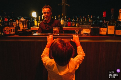 Little boy trying to look into the bar at the wedding in Long Beach, California, USA