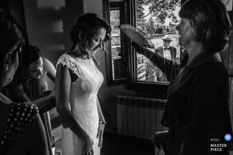 Bride getting cooled down while she gets help with her dress before the wedding ceremony in Guadalajara