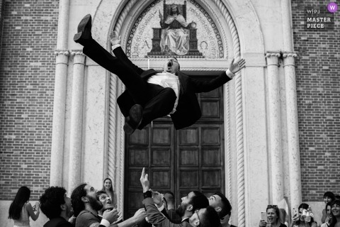 Guests throw the groom into the air at the wedding reception in Veneto, Italy