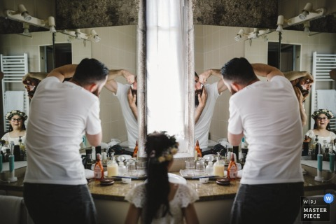 Portugal flower girl watches as the groom shaves before the wedding ceremony