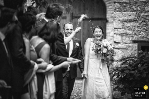 Guests throw rice at the bride and groom outside after the wedding ceremony in Borgo della Marmotta