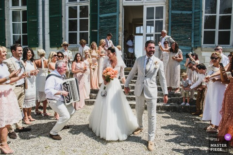 Bride and groom have confetti thrown at them at a wedding at Chateau de Juvigny in France