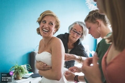 Bride laughs as she gets helps with her wedding dress before the ceremony in The Hague, the Netherlands