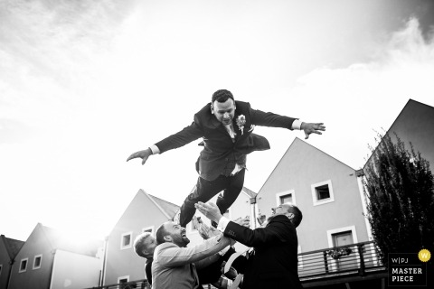 Groomsmen throw the groom into the air outside at the wedding reception in Prague