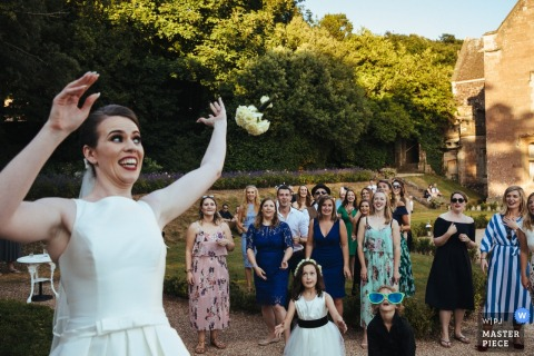 Guests wait as the bride throws the bouquet outside at the wedding reception in St Audries Park