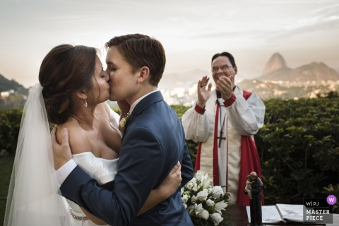 Outdoor photo of the priest clapping while the bride and groom kiss during the wedding ceremony in Rio de Janeiro, Brazil