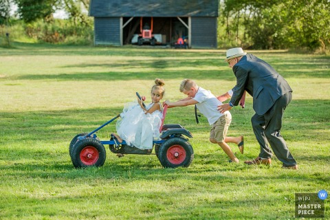 Netherlands guests having fun outside at the wedding reception pushing a gocart around the lawn