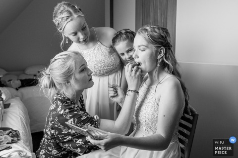 Netherlands bride getting her make up done while the flower girls watch before the ceremony