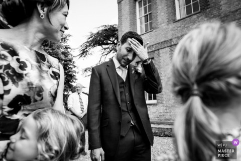Groom wipes the sweat off of his forehead outside at the wedding in Reading, UK