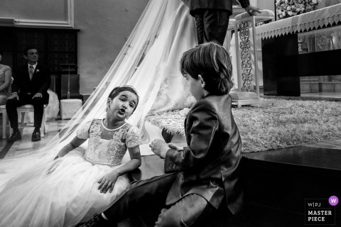 Flower girl and ring bearer talk to each other during the wedding ceremony in Goiânia