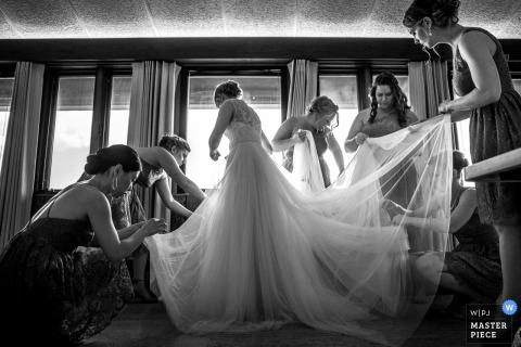 Le damigelle d'onore aiutano la sposa con il suo vestito prima della cerimonia presso l'UW Arboretum in questa foto in bianco e nero di un fotografo di matrimoni del Wisconsin.