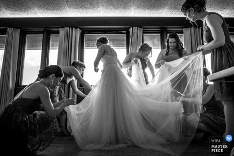 The bridesmaids help the bride with her dress before the ceremony at UW Arboretum in this black and white photo by a Wisconsin wedding photographer.