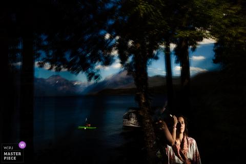 La novia se prepara frente a un lago con un kayak que pasa por el Parque Glaciar en esta foto de un fotógrafo de bodas de Montana.