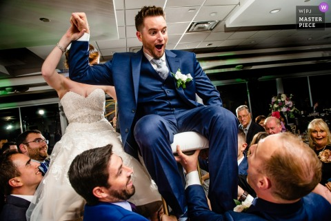 The bride and groom are lifted into the air on their chairs at The Estate at Farrington Lake in this photo by a New Jersey wedding photographer.