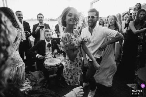 La fiesta de bodas baila mientras un músico toca el tambor detrás de ellos en esta foto en blanco y negro de un fotógrafo de bodas de Sydney, Australia.