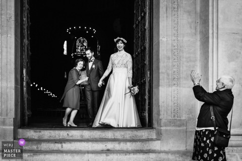 A woman applauds the bride and groom as they emerge from the ceremony in this black and white photo by a Paris, France wedding photographer.