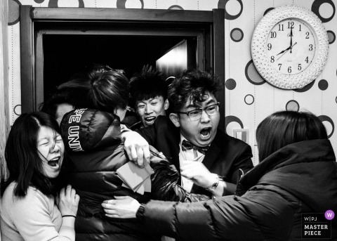 The groom and bridal party shout and celebrate in this black and white photo by a Beijing wedding photographer.