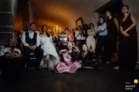 The bride, groom, and guests sit around a room laughing in the Chateau de Saulnat in this photo by a Lyon wedding photographer.