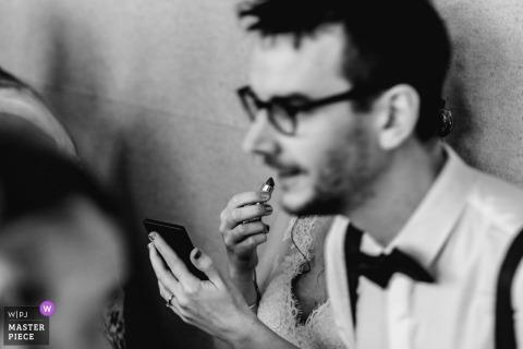 Ein Mann beugt sich vor und blockiert die Sicht der Braut, während sie auf diesem Schwarzweißfoto eines Frankfurter Hochzeitsfotografen Lippenstift aufträgt.