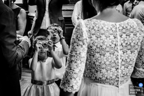 Black and white photo of two young children taking pictures of the bride by an Occitanie wedding photographer.