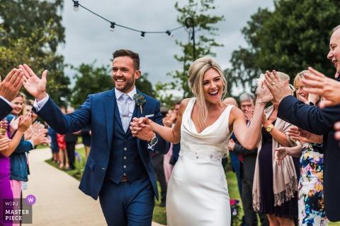 Braut und Bräutigam haben eine improvisierte Linie von 120 High Fives - private Haushochzeit in Großbritannien