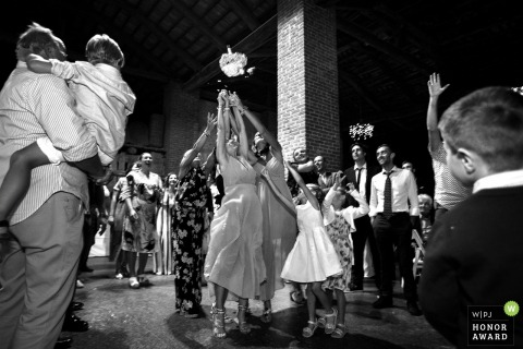 Guests try to catch the bouquet at the reception in Cavour
