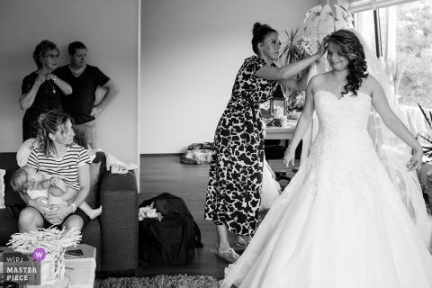 Eine Frau wird mit der Braut fertig, während andere Gäste in diesem Schwarzweiss-Foto von einem niederländischen Hochzeitsfotografen aufpassen.