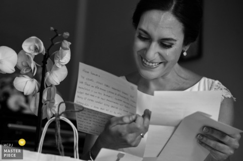 Black and white photo of the bride shedding a tear as she reads a letter by a Valencia, Spain wedding photographer.