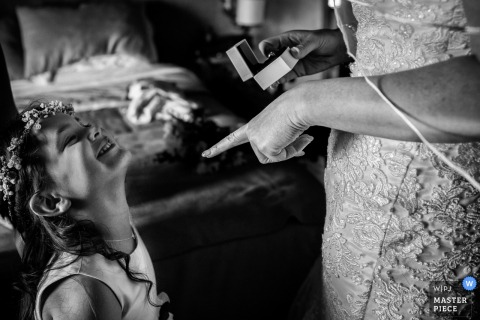 Black and white photo of a woman pointing at a smiling, young girl as she holds a ring in her other hand by an Umbria wedding photographer.