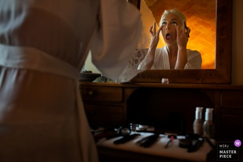 The bride makes faces in the mirror as she applies her makeup in this photo by a Florence wedding photographer.