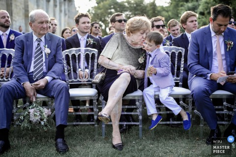 A woman leans over to kiss a young boy on the cheek during the ceremony in this photo by a Paris, France wedding photographer.