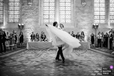The groom picks up his wife and spins her on the dance floor as guests watch in this black and white photo by a Paris wedding photographer.