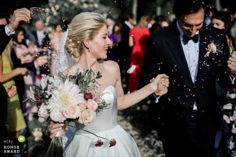 Abbaye de Royaumont - France outdoor wedding ceremony - bright and groom laugh as guests throw confetti at them