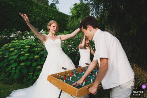 The bride cheers as she scores against her opponent in a game of foosball in this photo by a Paris, France wedding photographer.