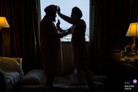 A man helps the groom prepare for the ceremony in his room in this photo by a New Delhi, India wedding photographer.