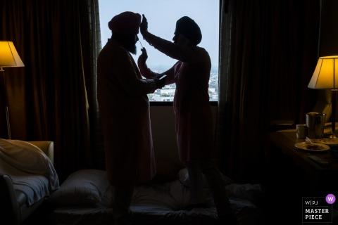 Een man helpt de bruidegom zich voor te bereiden op de ceremonie in zijn kamer op deze foto door een trouwfotograaf uit New Delhi, India.
