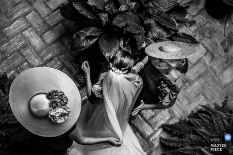 Black and white photo of the bride with two bridesmaids in hats admiring the plants in Ubeda by an Andalusia wedding photographer.