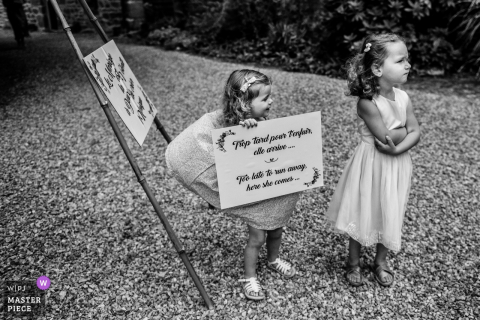 Two little girls stand outside as one holds a sign in this black and white photo taken outside of Le Clos de Trevannec in France by a Victoria, Australia wedding photographer.