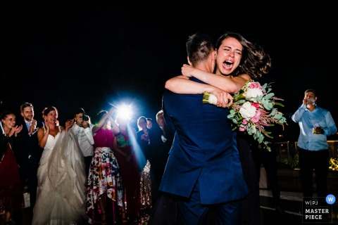 Photo of a just-engaged woman and man hugging each other during this Spain wedding as the bride, groom, and guests applaud by a Ho Chi Minh, Vietnam wedding photographer.